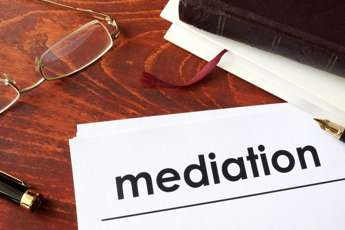 "A document titled ""Mediation"" on a wooden desk with glasses and a journal nearby"
